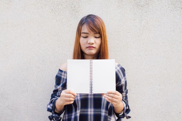 Bela jovem asiática que se esconde atrás de um livro em branco sobre o fundo da parede de concreto. imagens de estilo de efeito vintage.