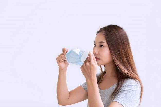 Bela jovem asiática segurando máscara protetora em fundo branco.