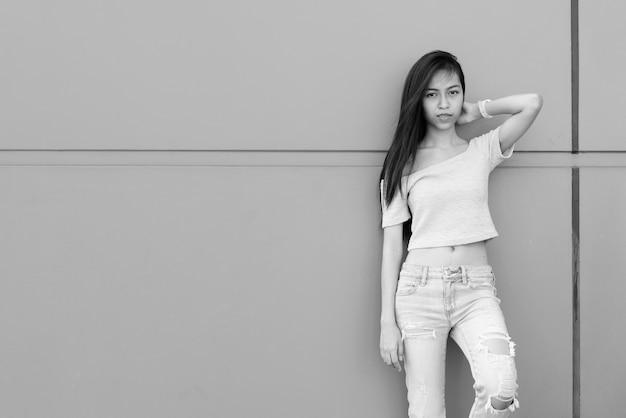 Bela jovem asiática segurando o cabelo enquanto se inclina na parede de concreto ao ar livre