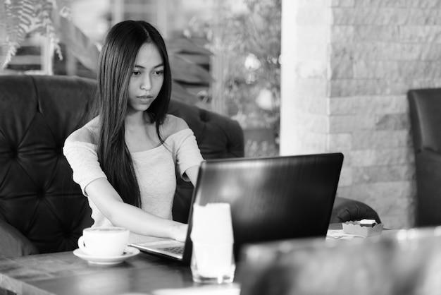 Bela jovem asiática sentada em um café ao ar livre enquanto usa o laptop com cappuccino na mesa de madeira