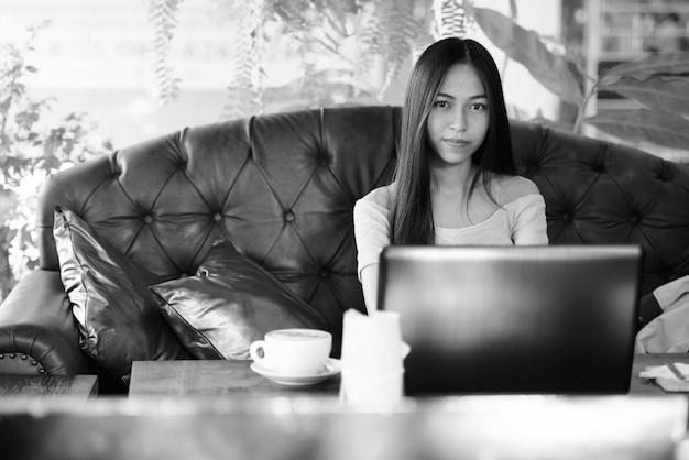 Bela jovem asiática sentada em uma cafeteria ao ar livre com um laptop e um cappuccino na mesa de madeira