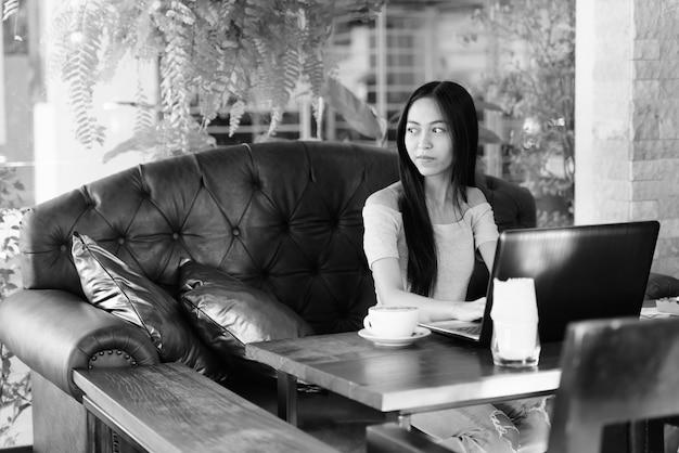 Bela jovem asiática sentada enquanto pensa em um café ao ar livre com o laptop na mesa de madeira
