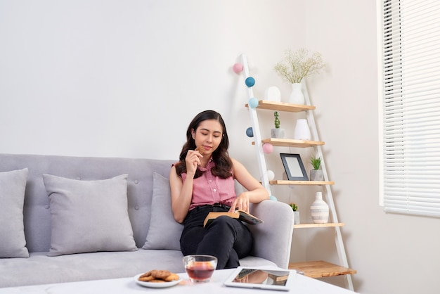 Bela jovem asiática sentada no sofá lendo um livro, saboreando seu chá na sala de estar em casa