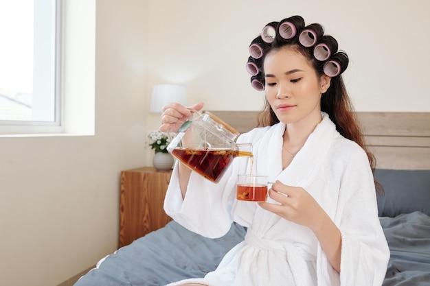 Bela jovem asiática servindo-se de uma xícara de chá de ervas após um banho relaxante