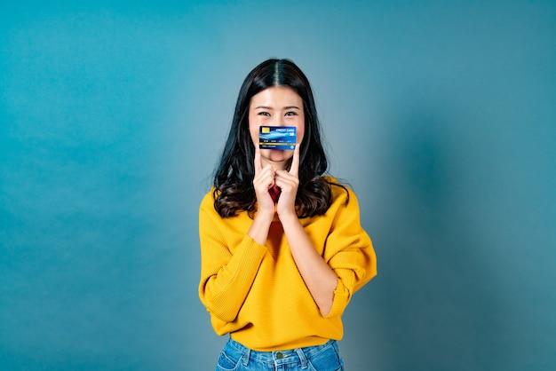 Bela jovem asiática sorrindo e apresentando o cartão de crédito na mão, mostrando confiança e segurança para fazer o pagamento