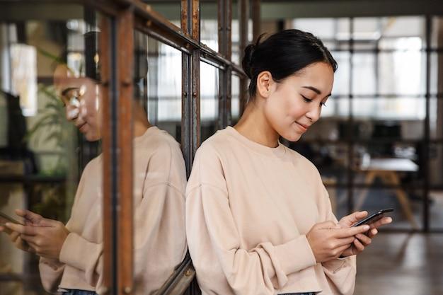 Bela jovem asiática sorrindo e segurando o celular enquanto trabalha no escritório