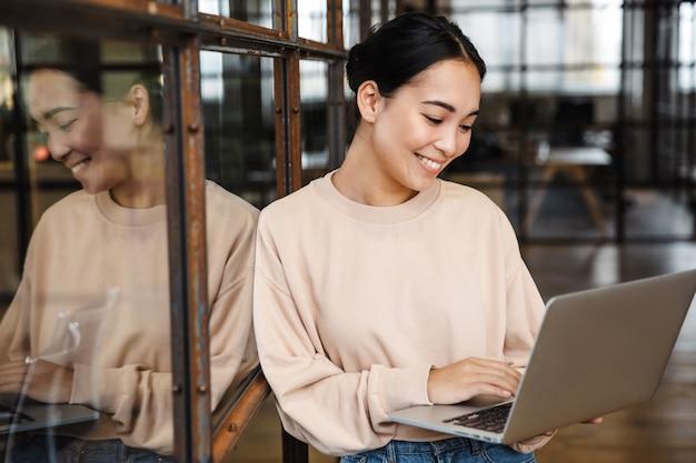 Bela jovem asiática sorrindo e segurando um laptop enquanto trabalhava no escritório