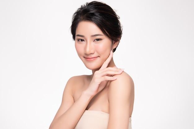 Bela jovem asiática tocando a bochecha macia e sorria com a pele limpa e fresca. felicidade e alegria com, isolado no branco, beleza e cosméticos,