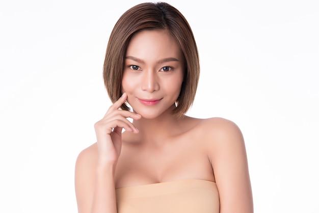 Bela jovem asiática tocando a bochecha macia e sorria com a pele limpa e fresca