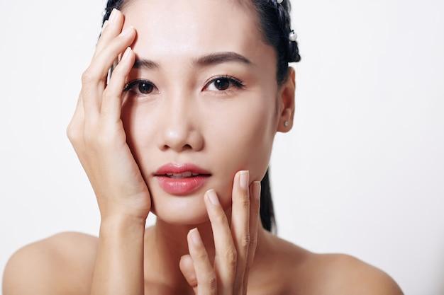 Bela jovem asiática tocando seu rosto e olhando para a frente