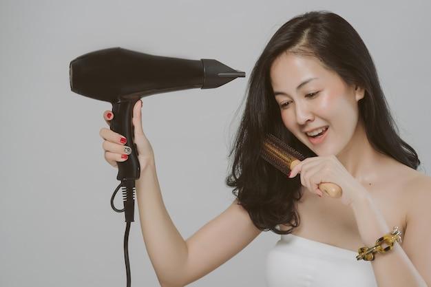 Bela jovem asiática usa secador de cabelo em fundo cinza