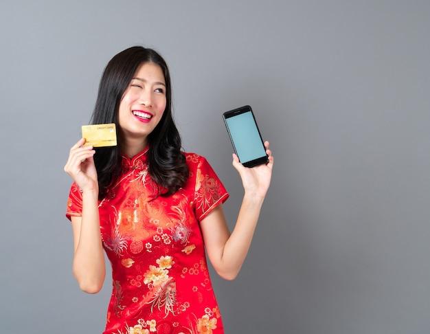 Bela jovem asiática usa um vestido chinês vermelho usando o smartphone e segurando um cartão de crédito na cor cinza