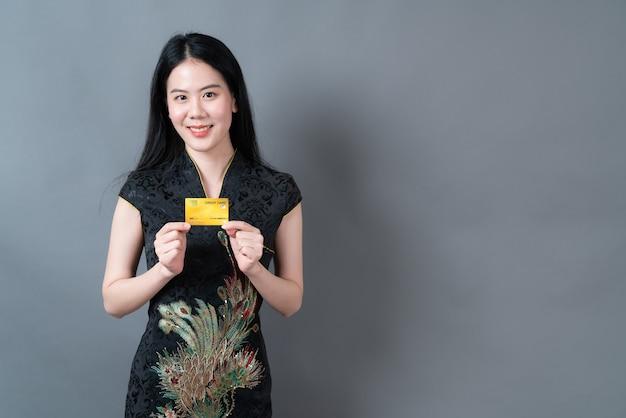 Bela jovem asiática usa um vestido preto tradicional chinês com a mão segurando um cartão de crédito na parede cinza