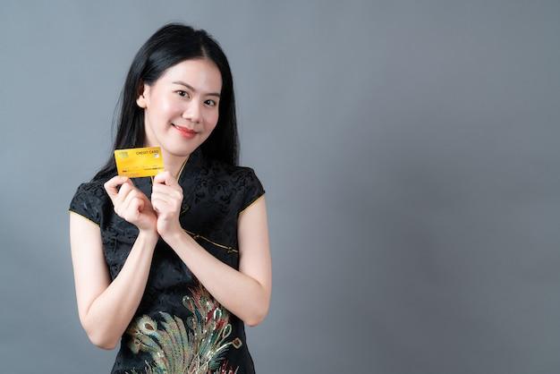 Bela jovem asiática usa um vestido preto tradicional chinês com a mão segurando um cartão de crédito na superfície cinza