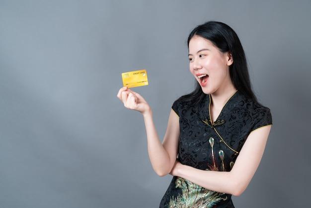 Bela jovem asiática usa um vestido preto tradicional chinês com a mão segurando um cartão de crédito no fundo cinza