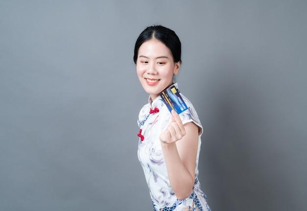 Bela jovem asiática usa um vestido tradicional chinês com a mão segurando um cartão de crédito no fundo cinza