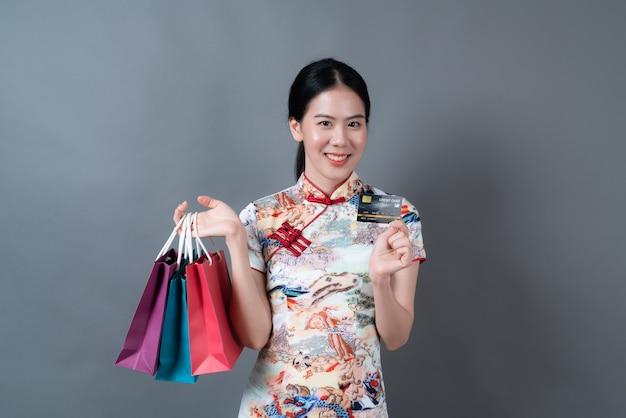 Bela jovem asiática usa um vestido tradicional chinês com sacola de compras e cartão de crédito na parede cinza