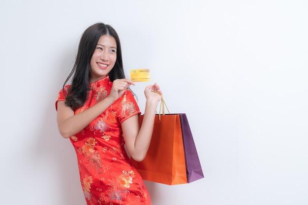 Bela jovem asiática usa um vestido tradicional chinês vermelho segurando um cartão de crédito e sacolas de compras para o ano novo chinês