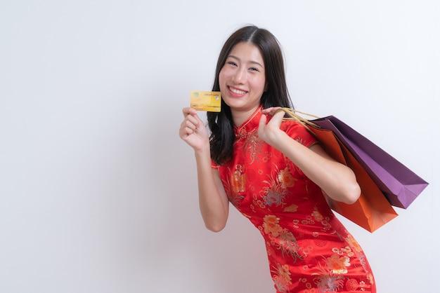 Bela jovem asiática usa um vestido tradicional chinês vermelho segurando um cartão de crédito e sacolas de compras