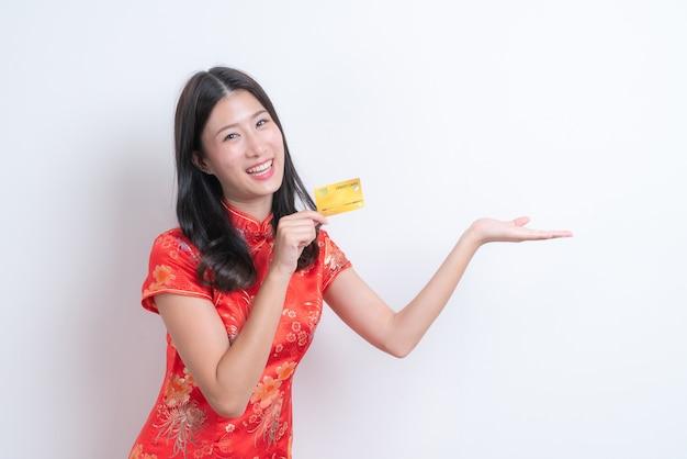 Bela jovem asiática usa um vestido tradicional chinês vermelho segurando um cartão de crédito no espaço branco