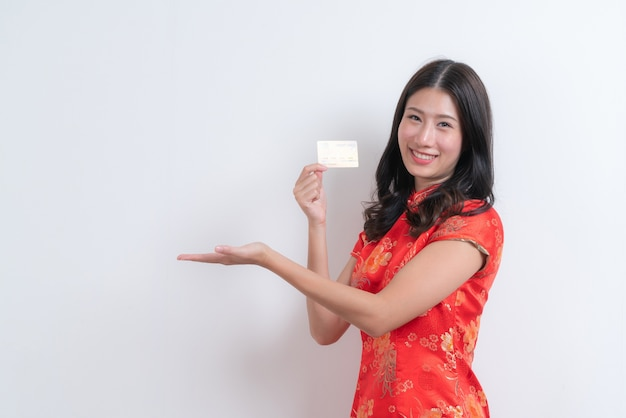 Bela jovem asiática usa um vestido tradicional chinês vermelho segurando um cartão de crédito para o ano novo chinês com espaço em branco e cópia