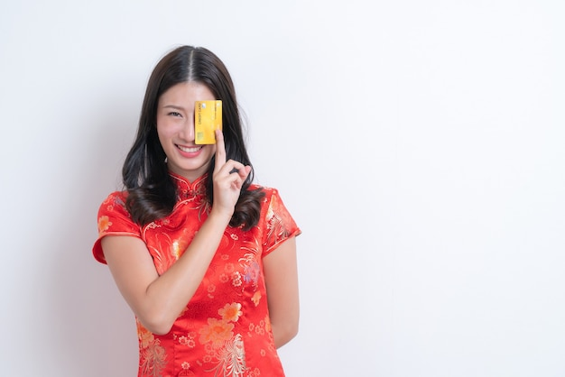 Bela jovem asiática usa um vestido tradicional chinês vermelho segurando um cartão de crédito para o ano novo chinês com uma parede branca e espaço de cópia