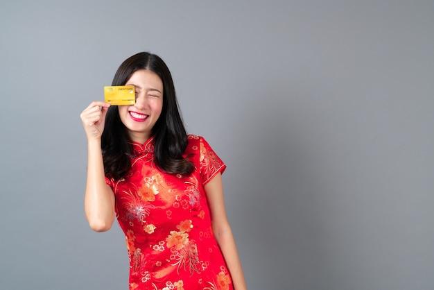 Bela jovem asiática usa um vestido vermelho chinês tradicional com a mão segurando um cartão de crédito cinza