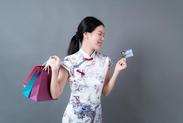 Bela jovem asiática usa vestido tradicional chinês com sacola de compras e cartão de crédito em fundo cinza