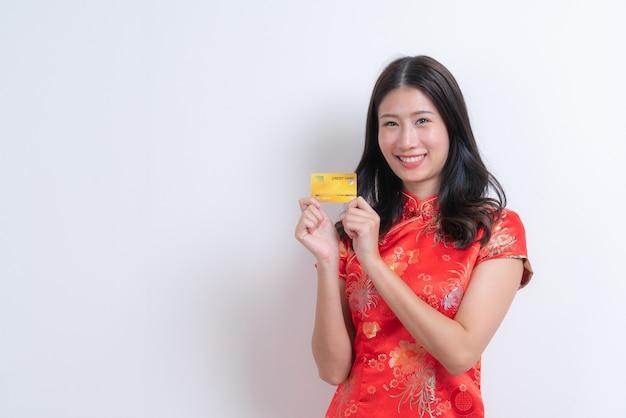 Bela jovem asiática usa vestido tradicional chinês vermelho segurando um cartão de crédito com espaço em branco e cópia