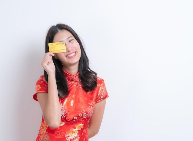 Bela jovem asiática usa vestido tradicional chinês vermelho segurando um cartão de crédito com fundo branco e espaço de cópia