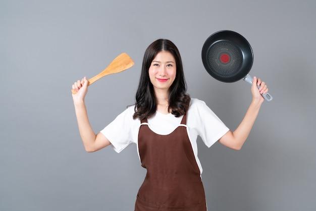 Bela jovem asiática usando avental com a mão segurando uma panela preta e uma espátula de madeira cinza