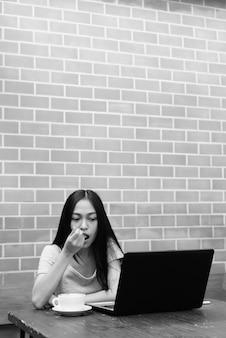 Bela jovem asiática usando laptop enquanto come a espuma do cappuccino na mesa de madeira na parede de tijolos