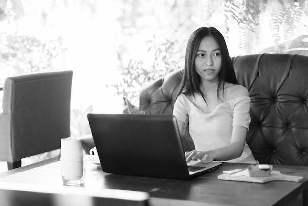 Bela jovem asiática usando laptop enquanto pensa e está sentada em uma cafeteria ao ar livre