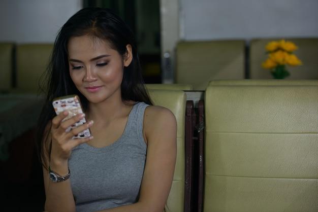Bela jovem asiática usando o telefone na cafeteria