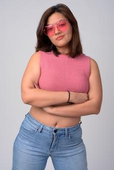 Bela jovem asiática usando óculos em formato de coração com os braços cruzados