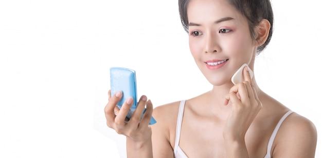 Bela jovem asiática usando pó, esponja e cosméticos no próprio rosto