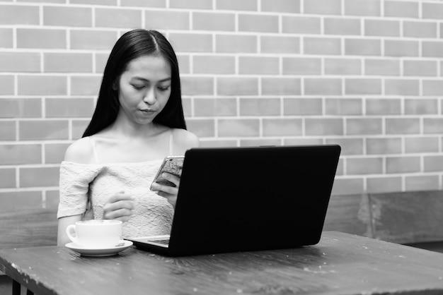 Bela jovem asiática usando telefone celular com laptop e cappuccino na mesa de madeira na parede de tijolos