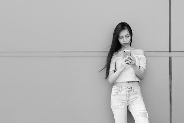 Bela jovem asiática usando telefone celular, em pé e encostada na parede de concreto ao ar livre