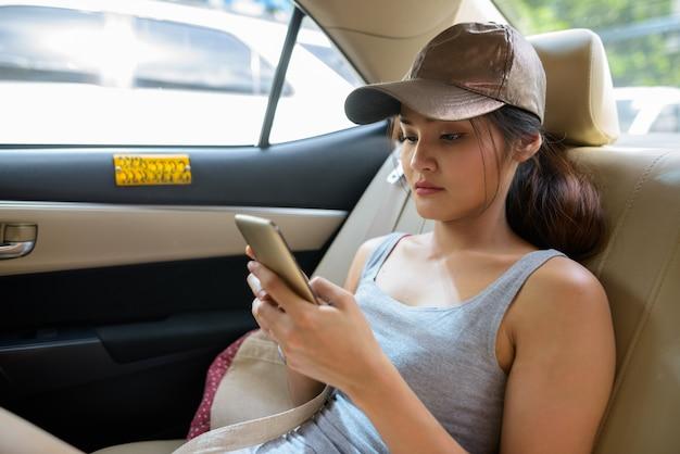 Bela jovem asiática usando telefone celular em um táxi