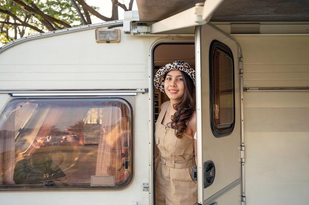 Bela jovem asiática usando um chapéu abre a porta do trailer com um sorriso no acampamento nas férias