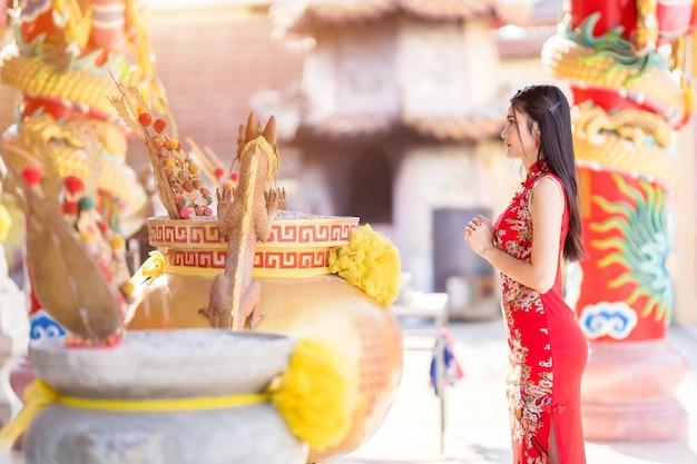 Bela jovem asiática usando um cheongsam chinês tradicional vermelho, rezando para a estátua de buda no festival de ano novo chinês no santuário chinês
