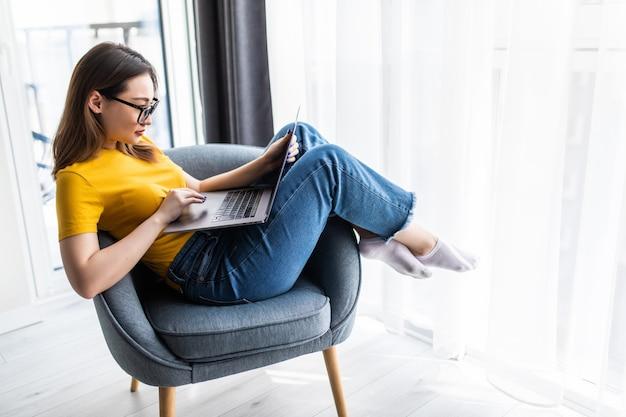 Bela jovem asiática usando um laptop, trabalhando online em casa e relaxando na poltrona