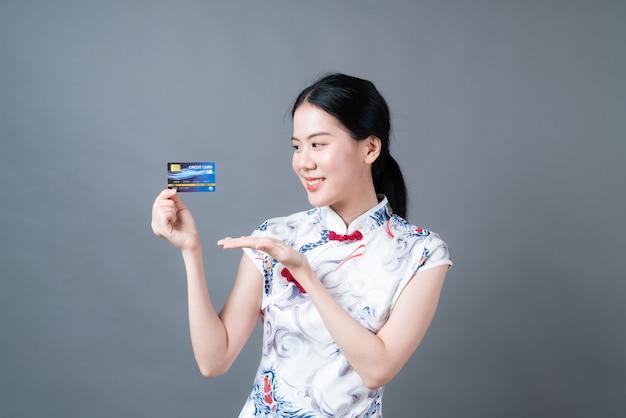 Bela jovem asiática usando um vestido tradicional chinês com a mão segurando um cartão de crédito na parede cinza