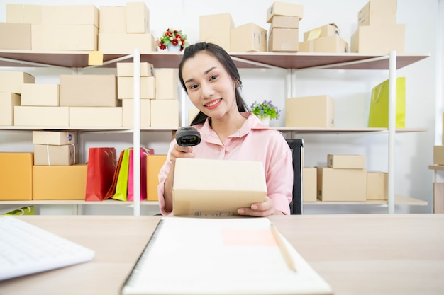 Bela jovem asiática vendendo produtos on-line. menina asiática bonita escrevendo o endereço em uma caixa de papel de encomendas.