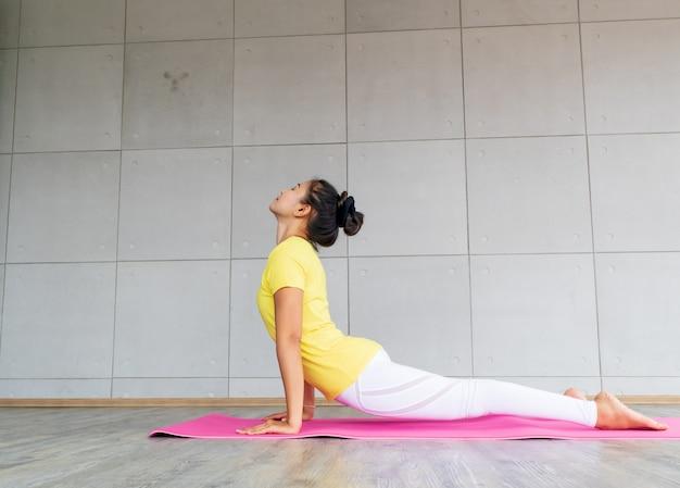 Bela jovem asiática vestindo roupas esportivas praticando ioga