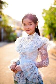 Bela jovem asiática vestindo roupas tradicionais tailandesas ao ar livre