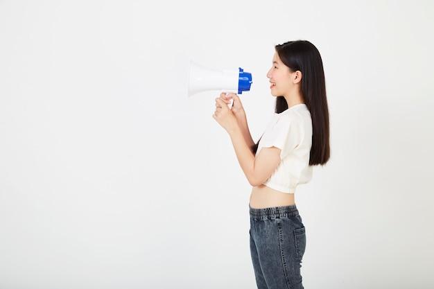 Bela jovem asiática vestindo uma camisa branca e jeans segurando um megafone expressando sucesso e ideias positivas em marketing ou vendas