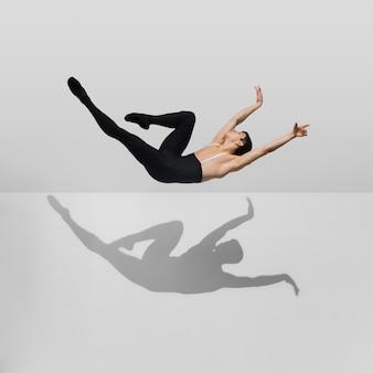Bela jovem atleta do sexo masculino praticando em estúdio branco com sombras em salto, ar voando
