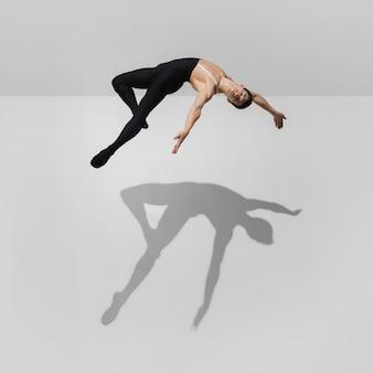 Bela jovem atleta do sexo masculino praticando no fundo branco do estúdio com sombras em salto, vôo do ar