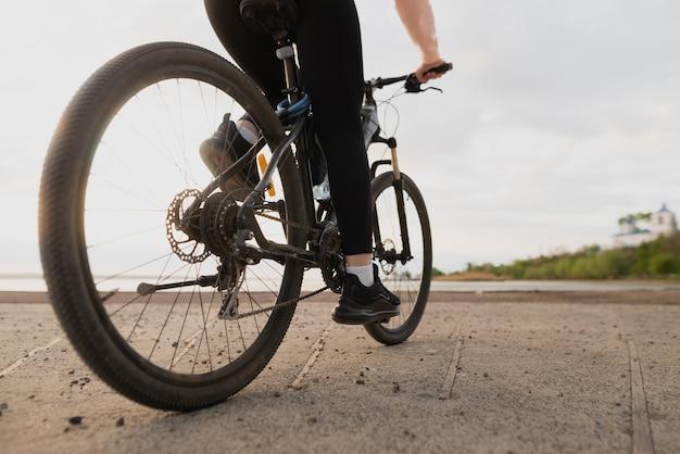 Bela jovem atleta entra para a prática de esportes e anda de bicicleta à beira-mar. perto de um pé feminino no pedal. lugar para texto